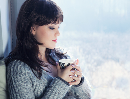 autumn young: Young beautiful brunette woman drinking coffee and wearing knitted cardigan sitting home relaxing by the window. Home chill out concept. Stock Photo