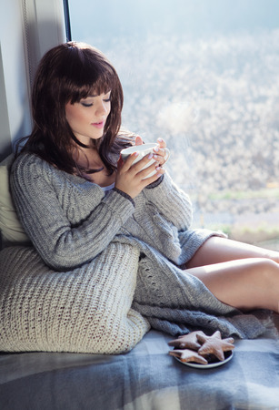 woman in bed: Young beautiful brunette woman drinking coffee and wearing knitted cardigan sitting home relaxing by the window. Home chill out concept. Stock Photo