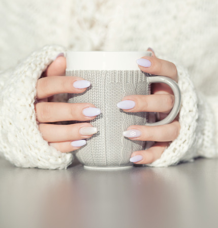 tea table: Close up of womans hands holding cup of hot coffee drink. She is wearing warm cardigan. Winter chill out and lifestyle concept.