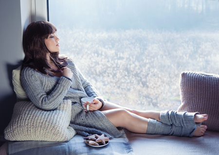 Young beautiful brunette woman with cup of coffee and gingerbread wearing knitted cardigan sitting home relaxing by the window. Home chill out concept.