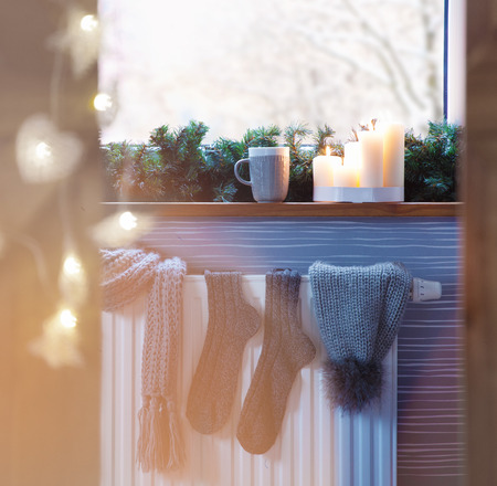 scandinavian christmas: Winter fashion accessories hat socks drying on a heater, christmas lights, snow window view and hot drink