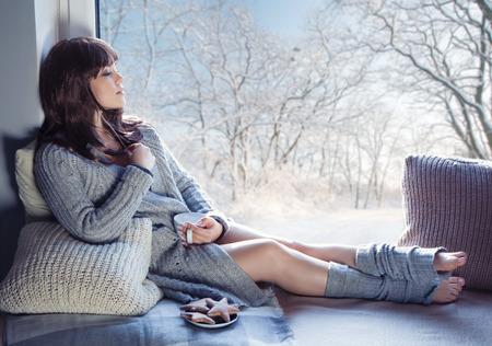 Jonge mooie brunette vrouw met een kopje koffie en ontbijtkoek dragen gebreid vest zitten thuis ontspannen bij het raam. Sneeuwwinter thuis chill out concept.