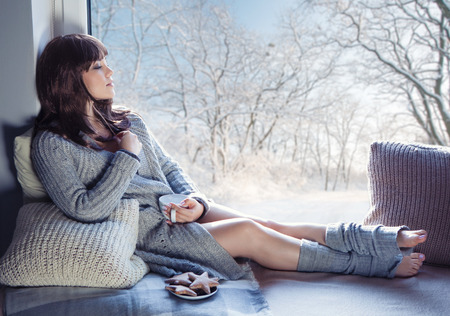 window: Young beautiful brunette woman with cup of coffee and gingerbread wearing knitted cardigan sitting home relaxing by the window. Snowy winter home chill out concept.