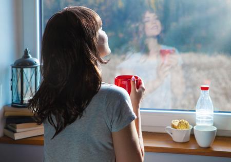 Jonge vrouw bedrijf kopje koffie thuis te zitten bij het raam. Gezicht reflectie op het glas Stockfoto