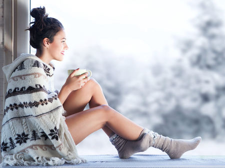 Young beautiful brunette woman drinking cup of coffee wearing knitted nordic print poncho sitting home by the window. Blurred winter snow tree background