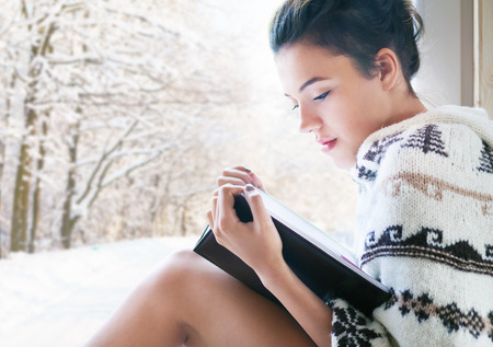 Beautiful young brunette woman reading book wearing knitted poncho sitting home by the window. Snowy winter forrest background. Zdjęcie Seryjne