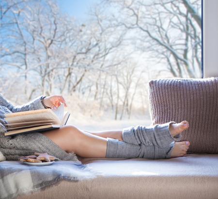 Junge schöne Brünette Frau mit Tasse Kaffee und Lebkuchen Tragen Strickjacke sitzt Hause entspannen am Fenster. Snowy Winter zu Hause chillen Konzept. Standard-Bild - 49400411
