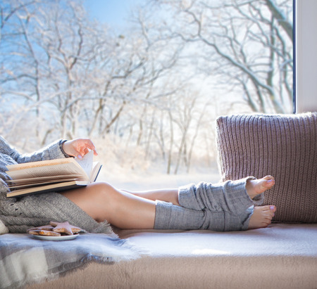 leg warmers: Young beautiful brunette woman with cup of coffee and gingerbread wearing knitted cardigan sitting home relaxing by the window. Snowy winter home chill out concept.