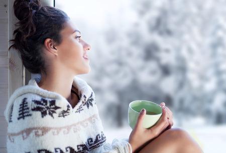 젊은 아름 다운 갈색 머리 여자 마시는 북유럽 인쇄 판 쵸 집 창 옆에 앉아 커피 한 잔 마시는. 흐리게 겨울 눈 나무 배경