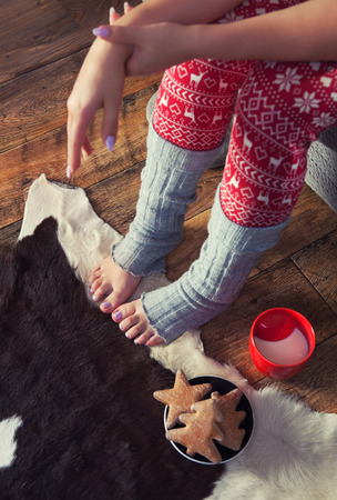 leg warmers: Close up of woman wearing Christmas print pajamas with hot milk and gingerbread. Winter xmas concept.