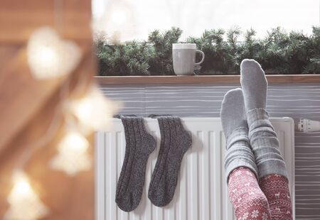 comfortable home: Woman warming up with feet on heater Winter woolen socks drying on a heater, christmas lights, decorations and hot drink