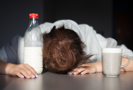 hangover: Tired woman with head on the table. Health issue, hangover or Monday morning concept