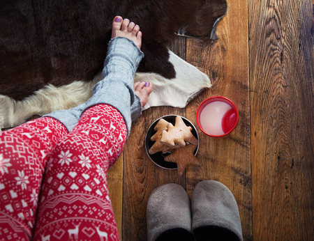 young girl feet: Close up of woman wearing Christmas print pajamas with hot milk and gingerbread. Winter Xmas concept.