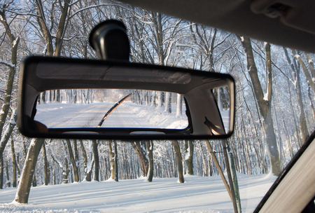 rear view: Car rear view mirror, winter snow forest landscape background