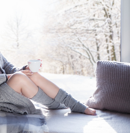 lipstick kiss: Young woman with cup of coffee wearing knitted cardigan sitting home relaxing by the window. Snowy winter home chill out concept Stock Photo