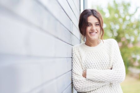 comfortable: Beautiful natural young brunette woman wearing knitted sweater by the house