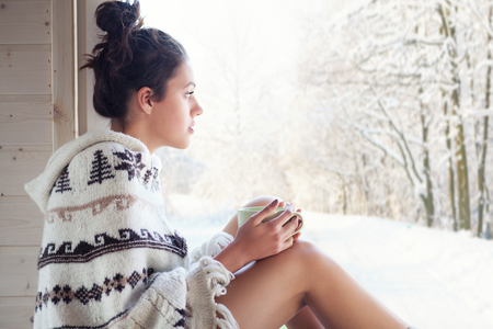 Young beautiful happy brunette woman drinking cup of coffee wearing knitted nordic print poncho chilling out home by the window. Winter forrest landscape background