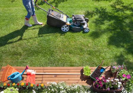 jardineros: Siega de la mujer con la cortadora de césped en el jardín, el concepto de jardinería