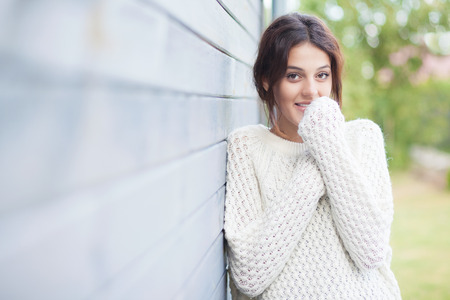 woman young: Beautiful shy natural young brunette smiling woman wearing knitted sweater by the house.