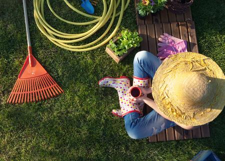 Vrouw die een koffie pauze tijdens het werken in de tuin