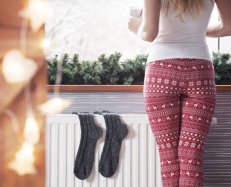 Woman warming up with hot coffee. Winter woolen socks drying on a heater, christmas lights, decorations