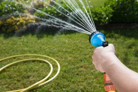 hand van de vrouw met een tuinslang water geven planten en gazon