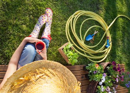 hose: Mujer que tiene un descanso para tomar café mientras se trabaja en el jardín
