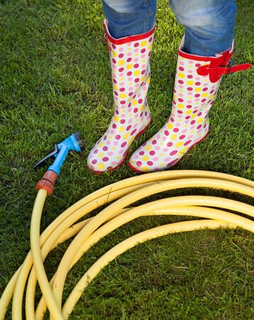 wellies: Woman wearing colorful wellies with garden water hose