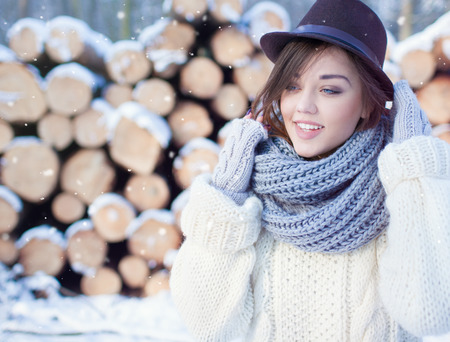 fedora hat: Beautiful young smiling woman, wearing knitted scarf and fedora hat covered with snow flakes. Pile of pine logs in the background. Snowing winter beauty and fashion concept. Stock Photo