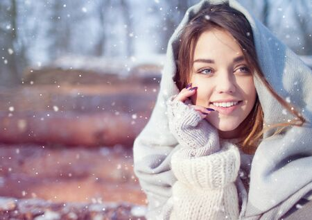 young beautiful woman: Beautiful smiling happy young woman covered in blanket and snow flakes sitting on pile of pine logs. Snowing winter outdoor leisure concept.