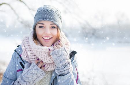 아름 다운 행복 눈 조각으로 덮여 겨울 모자 장갑과 스카프를 착용하는 젊은 여자를 웃고. 겨울 숲 풍경 배경