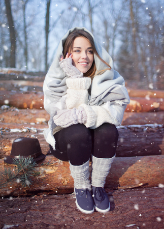 warmers: Beautiful happy young woman covered in blanket and snow flakes sitting on pile of pine logs. Snowing winter outdoor relax concept.