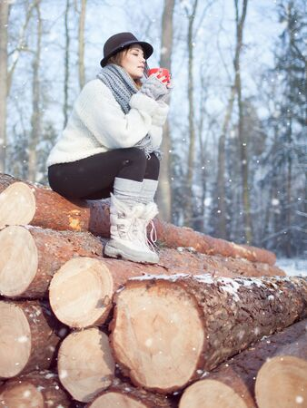 winter fashion: Beautiful young woman holding hot drink wearing knitted scarf, fedora hat and winter boots covered with snow flakes. Sitting on pile of pine logs. Snowing winter fashion concept.