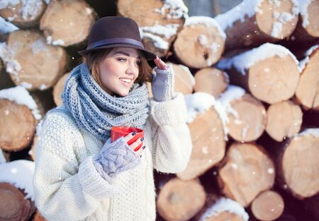 fedora hat: Beautiful young happy woman holding hot drink wearing knitted scarf and fedora hat covered with snow flakes. Pile of pine logs in the background. Snowing winter beauty and fashion concept.