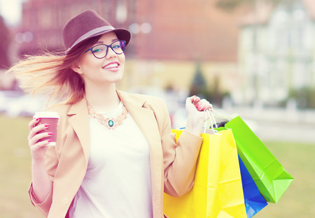 happy shopper: Young attractive happy shopper woman wearing hat and glasses holding shopping bags