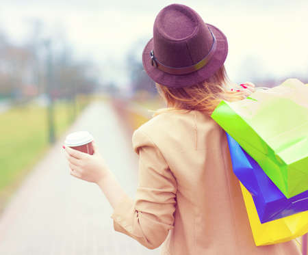 take away: Young shopper woman wearing hat glasses holding shopping bags