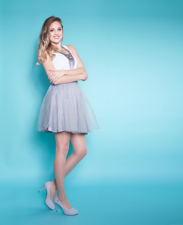 beauty full: Full body portrait of young attractive blonde smiling woman wearing dress and high heels over a blue background