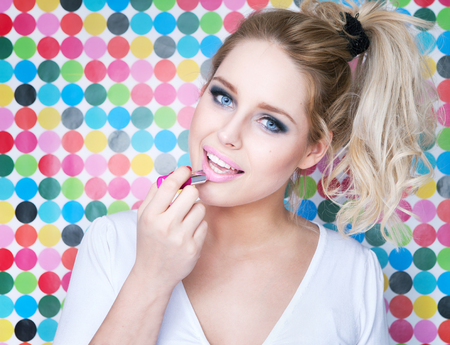 make: Attractive blonde young woman putting on lipstick on spotted background, make up beauty and fashion concept