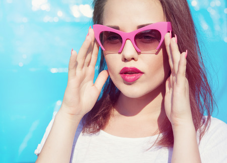 summer beauty: Colorful portrait of young attractive woman wearing sunglasses. Summer beauty and nail art concept