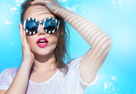 Kleurrijk portret van jonge aantrekkelijke vrouw draagt een zonnebril. De zomer schoonheid en nail art-concept