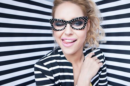 Attractive winking young blonde woman wearing glasses on stripy background, beauty and fashion concept