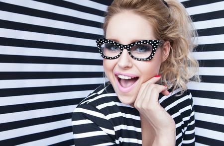 Aantrekkelijke verrast jonge blonde vrouw draagt een bril op gestreepte achtergrond, schoonheid en mode-concept