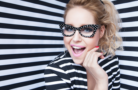Attractive surprised young blonde woman wearing glasses on stripy background, beauty and fashion concept Foto de archivo