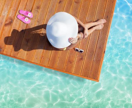 여름 휴가 패션 개념 - 여자 위에서 목조 부두 샷 수영장에서 태양 모자를 입고 선탠