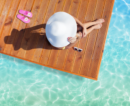 Summer holiday fashion concept - tanning woman wearing sun hat at the pool on a wooden pier shot from above