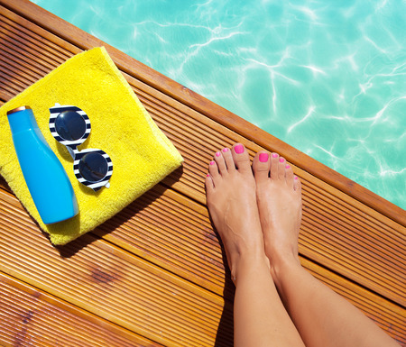 sunnies: Summer holiday fashion selfie concept - woman on a wooden pier at the pool with summer accessories; sunglasses, towel Stock Photo
