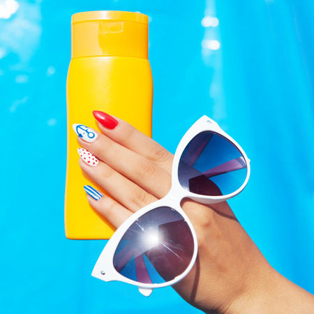 Summer fashion and beauty hand care concept, woman with marine sailor gel nails holding sunglasses and sunscreen lotion Standard-Bild