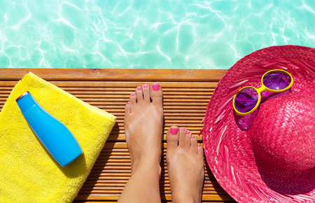 Summer holiday fashion selfie concept - woman on a wooden pier at the pool with summer accessories; sunglasses, straw hat, towel and sun lotion