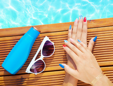 bracelet tattoo: Woman lying down by the pool, marine sailor gel nails close up summer beauty concept
