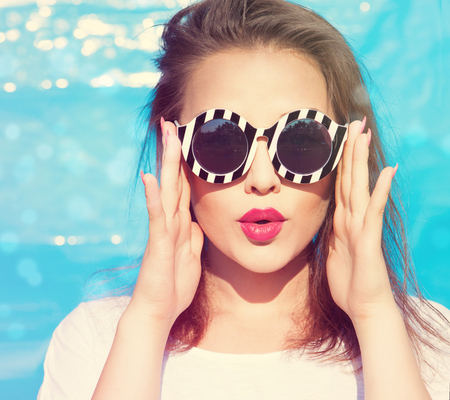 Colorful portrait of young attractive surprised woman wearing sunglasses. Summer beauty concept 스톡 콘텐츠
